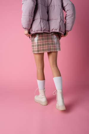 back view of young woman in stylish winter outfit on pink background