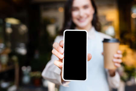 young florist holding smartphone with blank screen and coffee to go on blurred background