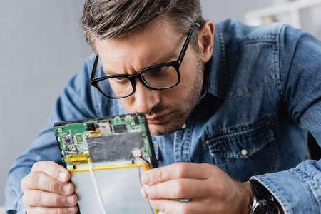 Focused repairman in eyeglasses looking at part of broken digital tablet