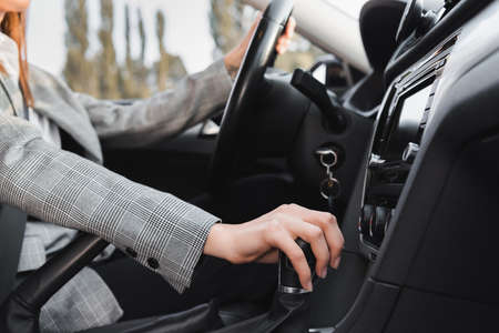 cropped view of businesswoman shifting gear lever while driving car on blurred background Foto de archivo