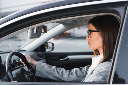 side view of businesswoman in eyeglasses looking ahead while driving car Stock Photo