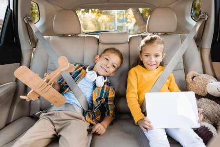 Cheerful kids with toys and digital tablet on back seat of auto