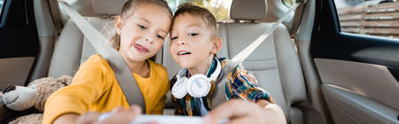 Children with headphones and toy taking selfie on smartphone in car, banner
