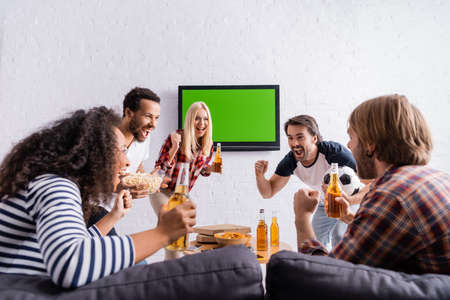 excited football fans holding beer and showing winner gesture near lcd tv on wall