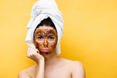sad beautiful woman with towel on head and coffee mask on face isolated on yellow