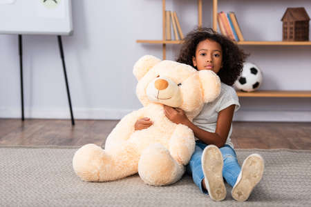 Upset african american girl with autism looking at camera and hugging teddy bear while sitting on floor with blurred office on background