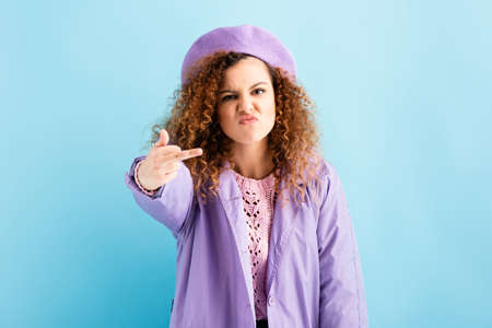 angry woman in beret showing middle finger on blue