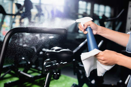 cropped view of charwoman spraying detergent while cleaning exercising machine in gym