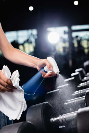 cropped view of charwoman spraying cleanser while cleaning dumbbells in gym Zdjęcie Seryjne