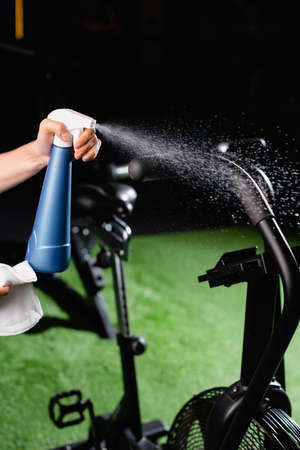 partial view of charwoman spraying cleanser on sports equipment in gym