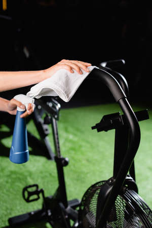 cropped view of charwoman wiping exercising machine in sports center