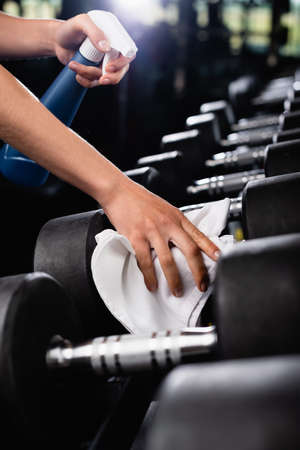 partial view of charwoman wiping dumbbells with rag while holding spray bottle on blurred foreground