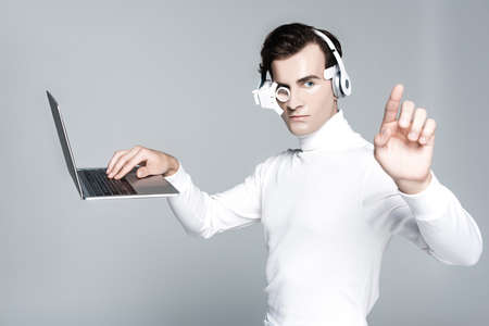 Cyborg man in headphones touching something while using laptop in air isolated on gray