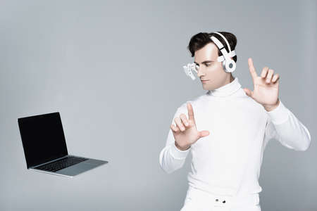 Cyborg in headphones touching something and looking at laptop with blank screen in air isolated on gray