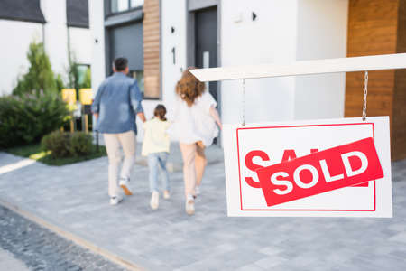 Back view of family going to house near sign with sold lettering on blurred background