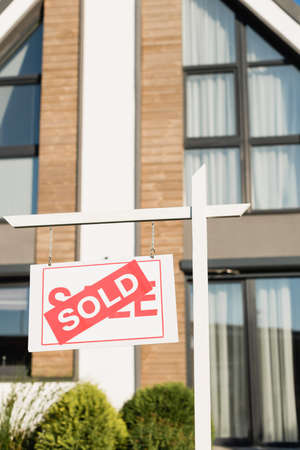 Sign with sold lettering with blurred front facade of modern house on background