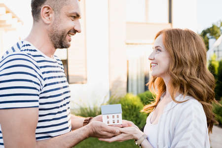Side view of happy couple looking at each other while holding statuette of house on blurred background