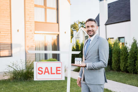 Smiling real estate agent with house statuette looking at camera near sign with sale lettering with blurred building on background