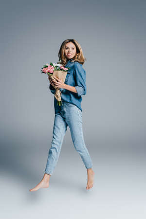 excited barefoot woman in denim shirt and jeans levitating with bouquet on gray