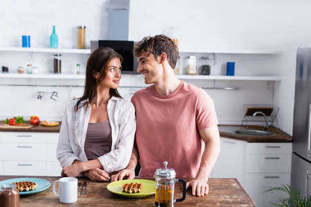 Smiling man standing near girlfriend, waffles and tea on kitchen table