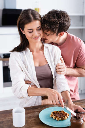 Man hugging smiling girlfriend near chocolate spread and waffle on table