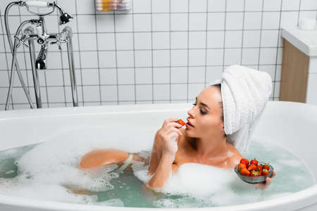 Young woman with towel on head eating strawberry in bath with soapsuds Foto de archivo
