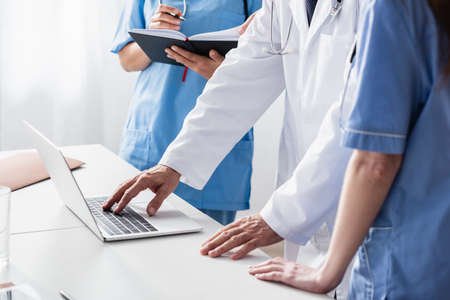 Cropped view of doctor in white coat using laptop near nurses with notebook Imagens