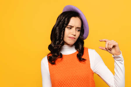 Displeased brunette woman in beret showing small amount gesture isolated on yellow