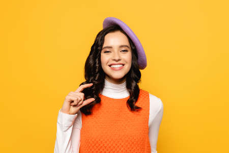 Smiling brunette woman in beret showing small amount gesture while looking at camera isolated on yellow