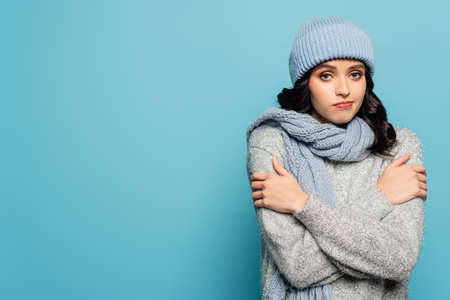 Sad brunette woman in hat and scarf hugging herself while looking at camera isolated on blue