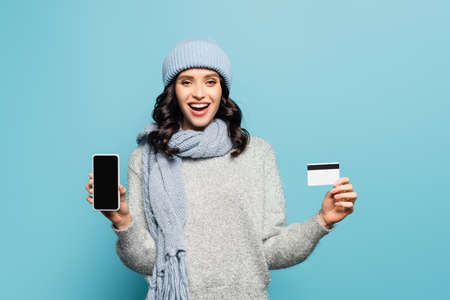 Excited brunette woman in winter outfit showing smartphone and credit card while looking at camera isolated on blue Banque d'images
