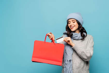 Cheerful brunette woman in scarf and hat putting credit card in red shopping bag isolated on blue Reklamní fotografie