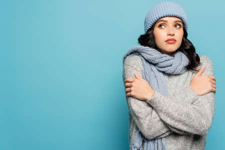 Brunette woman in winter outfit hugging herself while looking away isolated on blue