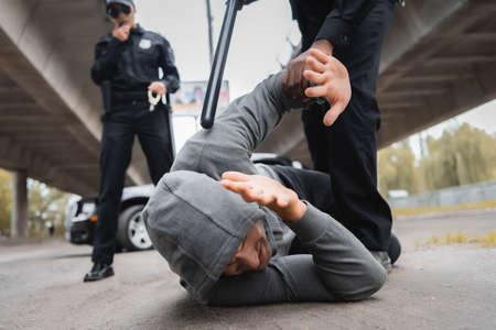 african american policeman with truncheon arresting hooded offender covering face while lying on street on blurred background Banque d'images