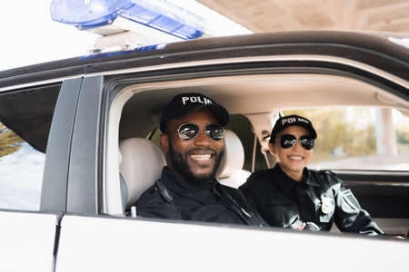 smiling multicultural police officers looking at camera on blurred background in patrol car
