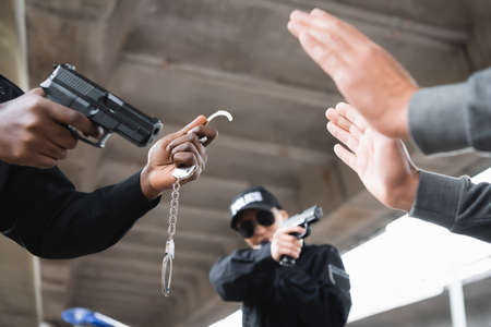 multicultural police officers aiming by pistols at surrendered offender on blurred foreground outdoors