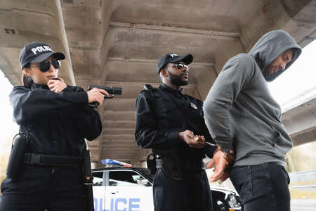 african american policeman handcuffing offender while colleague aiming with pistol near patrol car on urban street