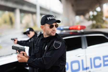 Policeman in sunglasses holding gun and looking away near colleague and car on blurred background