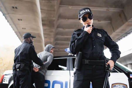 policewoman in sunglasses talking on radio set near african american colleague arresting offender on blurred background Banque d'images