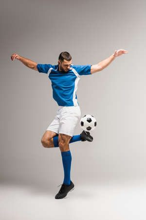 Athletic man exercising with football on gray background