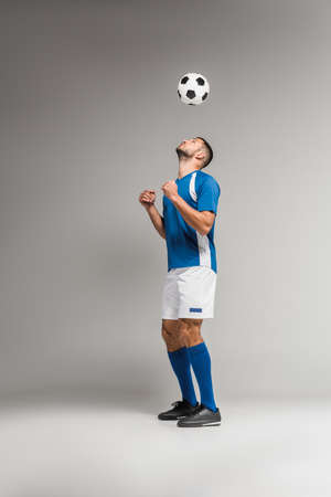 Young sportsman looking at football in air on gray background