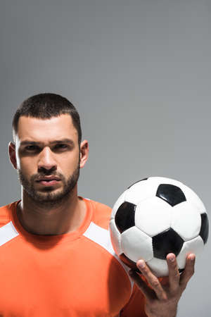 Football in hand of young sportsman isolated on gray