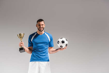 Cheerful sportsman holding football and golden champions cup on gray background