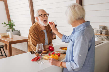 back view of elderly wife feeding happy husband with cherry tomato near table with food in kitchen