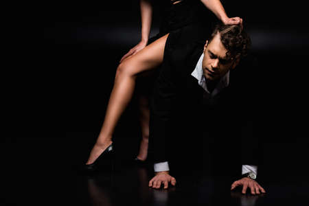 dominant woman in dress sitting of submissive man on all fours and pulling hair on black