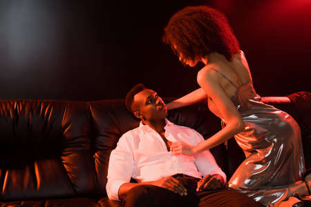 curly african american woman in dress seducing man in formal wear sitting on sofa on black Archivio Fotografico