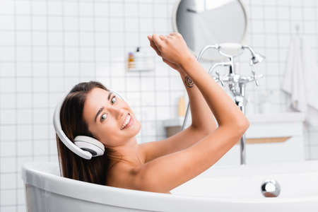 cheerful woman smiling at camera while taking bath and listening music in wireless headphones Banque d'images