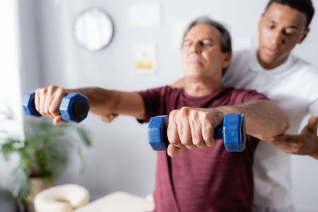 middle aged man exercising with dumbbells near african american physiotherapist on blurred background