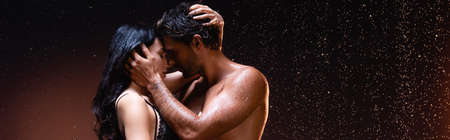 side view of couple embracing and kissing under rain on dark background, banner