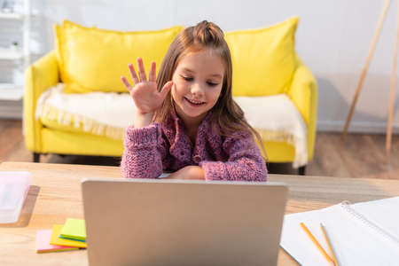 Smiling girl with waving hand looking at laptop on desk with stationery on blurred foreground